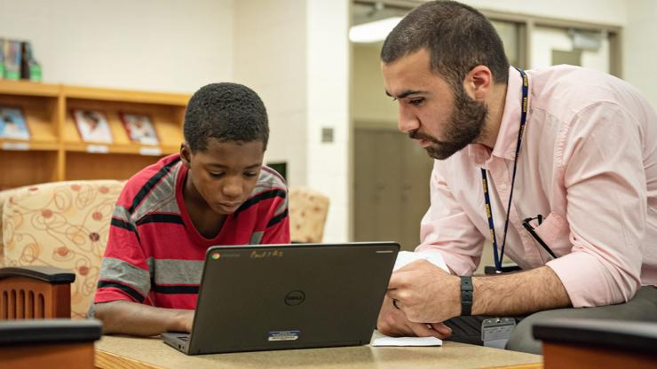 A male teacher helps a male student at a laptop