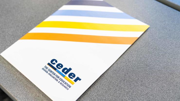 CEDER-branded folder on a grey desk